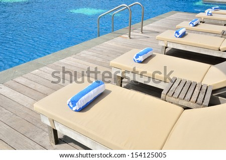 Empty sunbeds by the resort pool - stock photo