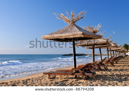 empty sunchairs and umbrellas on the sunny beach - stock photo