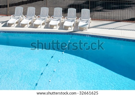 Empty swimming pool with lounge chairs on deck - stock photo