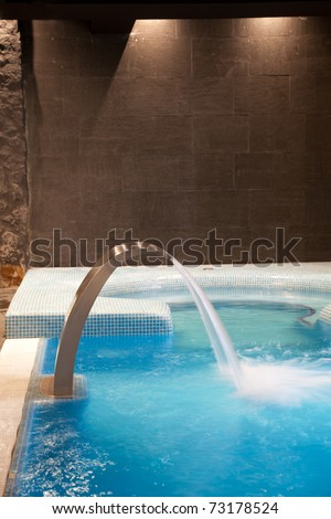 Empty Swimming pool with waterfall jet and jacuzzi in action - stock photo