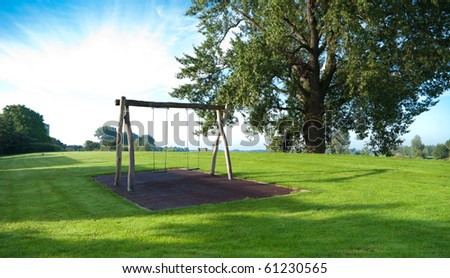 empty swing on a green hill - stock photo