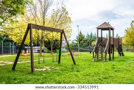 empty swings at playground for child near children stairs slides equipment, on green meadow background