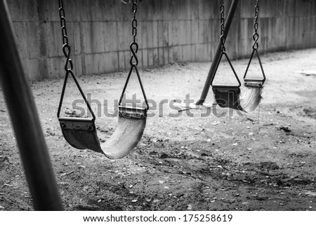 empty swings in black and white remind of childhood memories - stock photo
