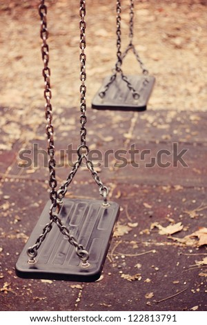 Empty swings on playground - stock photo