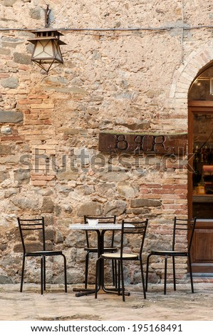 Empty table and chairs with 'Bar' sign above in San Marino city. - stock photo