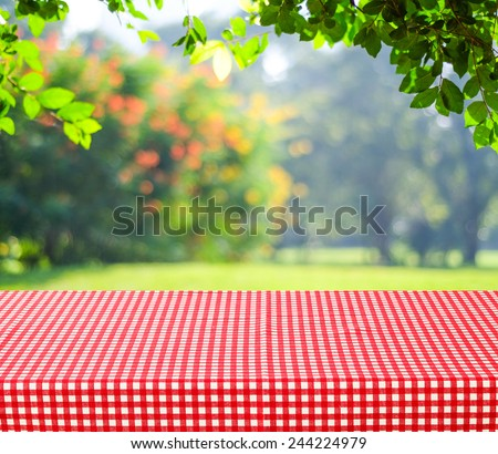 Empty table and red tablecloth with blur green leaves bokeh background, for product display montage - stock photo