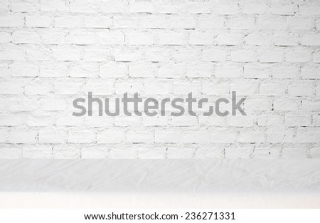 Empty table covered with wrinkled tablecloth over white brick wall background, for product display montage - stock photo