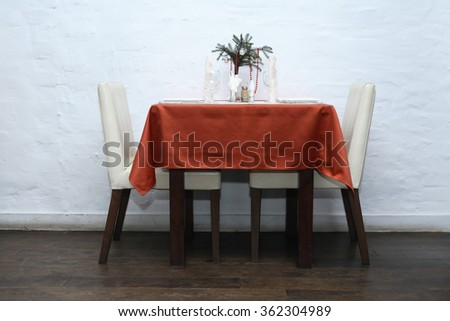 Empty table for two and chairs against white wall in restaurant - stock photo