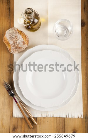 empty table set , olive oil, fresh bread, on wooden background - stock photo