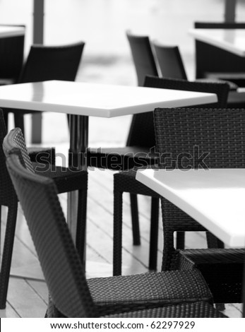 Empty tables and chairs in a outdoor cafe,shallow focus,black and white - stock photo