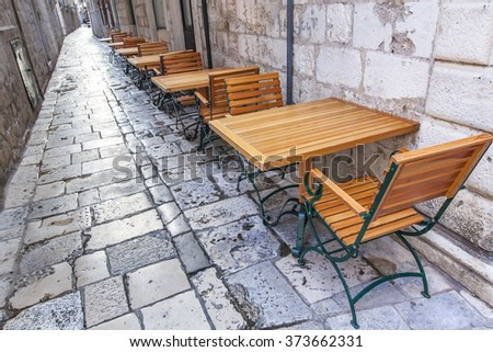 Empty tables and chairs of outdoor restaurant in heart of Dubrovnik old town, Europe - stock photo