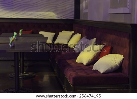 Empty tables and comfortable upholstered benches with cushions in a bar or nightclub in dim light - stock photo