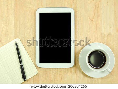 empty tablet computer and a cup of coffee on the desk