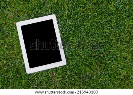 empty tablet on grass - stock photo