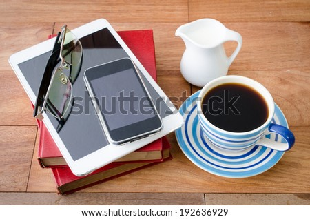 empty tablet pc and a coffee and Mobile phone with book on the office desk