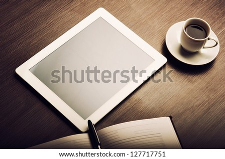 empty tablet pc and a coffee and notebook with pen on the office desk - stock photo