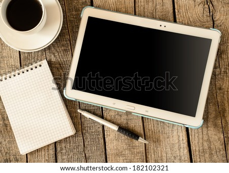 Empty tablet pc and a coffee and notebook with pen on wood table