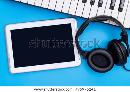 Empty Tablet screen with headphone and keyboard on blue background