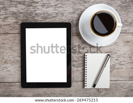 empty tablet with note paper and coffee on the wooden table