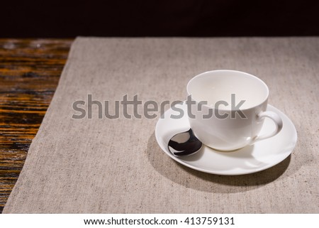 Empty teacup with stainless steel spoon on saucer over gray tablecloth and part of wooden table in background - stock photo