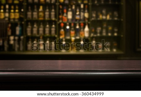 Empty the top of wooden table with  blurred counter bar and  bottles Background /for your product display - stock photo