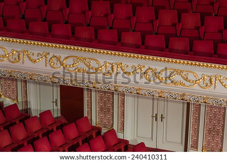 Empty theater with red chairs.