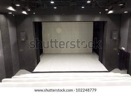 Empty theatre hall with covered seats - stock photo