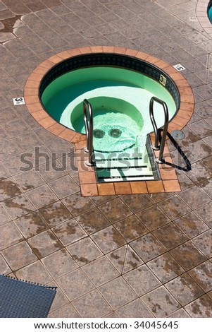Empty three and a half foot deep mineral hot springs pool - stock photo
