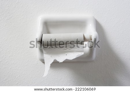 empty toilet paper roll on white wall - stock photo