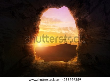Empty tomb with three crosses on a hill side. - stock photo