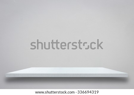 Empty top of white wooden shelf on grey cement wall. For product display