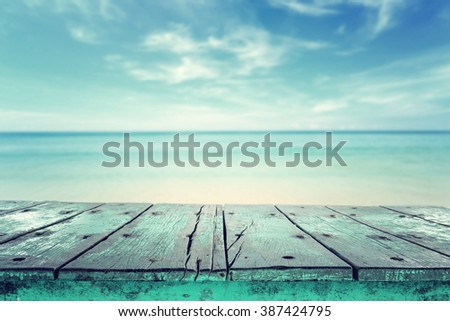 Empty top of wooden table and view of tropical beach background. For product display   - stock photo