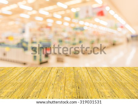 Empty top surface old yellow wooden table and blurred image of shopping mall with no people for background usage . - stock photo