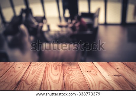 Empty top wooden table with defocus or blurred image of cafeteria background. For product display - stock photo