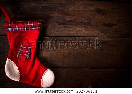 Empty traditional Christmas sock on wooden background with blank space - stock photo