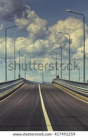 Empty transit road with highway lamp posts over cumulus clouds in the sky. - stock photo