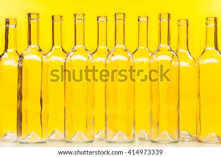 Empty transparent glass bottles over yellow wall - stock photo