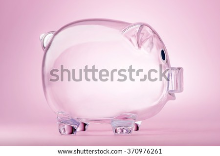 Empty transparent piggy bank on pink background