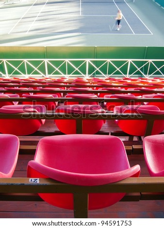 Empty tribune with red seats over tennis court - stock photo