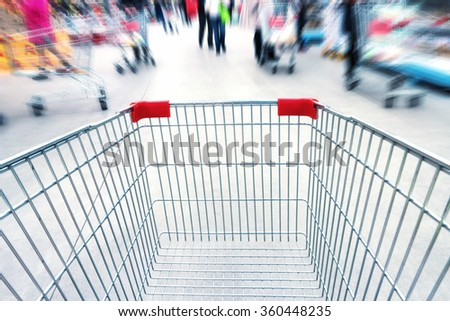 Empty trolley in supermarket or mall full of crowded people. Blur motion. - stock photo