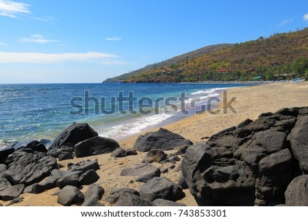 Empty tropical beach, sand and big stones. Exotic island shore with sandy beach and green hills.