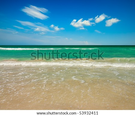Empty tropical ocean beach with set of clouds over water - stock photo