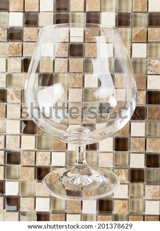 Empty  Tumbler for whiskey or brandy over  Mosaic Stones  Background  - stock photo