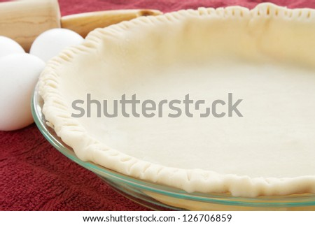 empty uncooked pie crust with raw eggs and a wooden rolling pin in the background. Selective focus on the pie crust. - stock photo