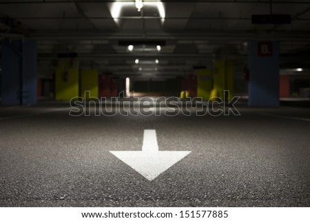 Empty underground car park. White arrow sign and spotlight on it. Close up.