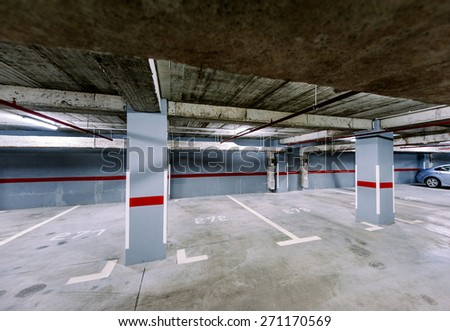 Empty underground car park with a solitaire car in the right corner - stock photo