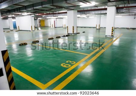 Empty underground parking garage at night - stock photo