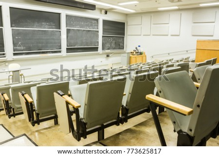 Empty University Classroom With Rows Of Desks And Chalkboards