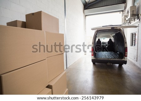 Empty van ready to be loaded in a large warehouse - stock photo