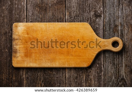 Empty vintage cutting board on dark wooden background - stock photo